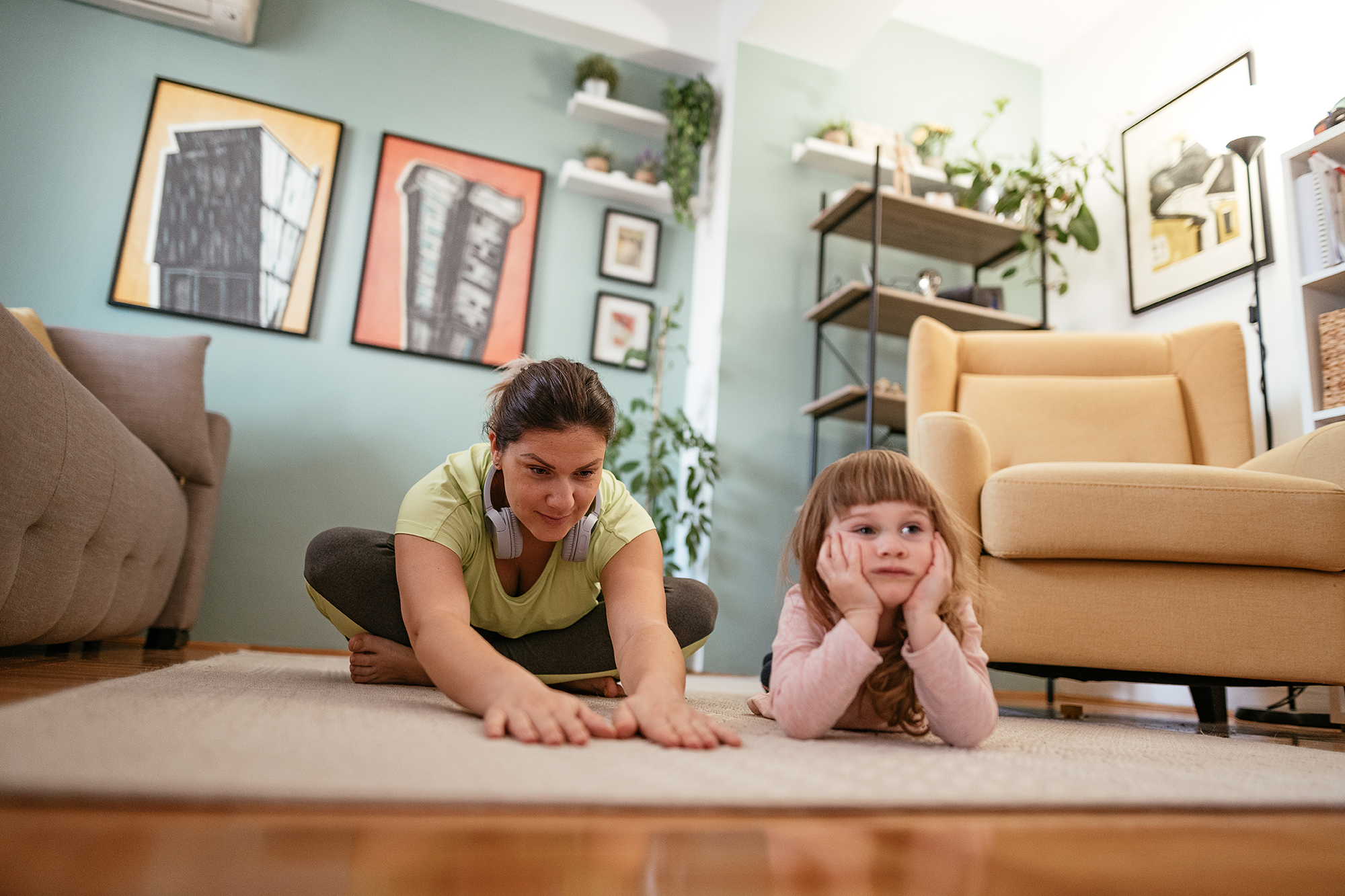 Adult woman exercising at home during quarantine with daughter