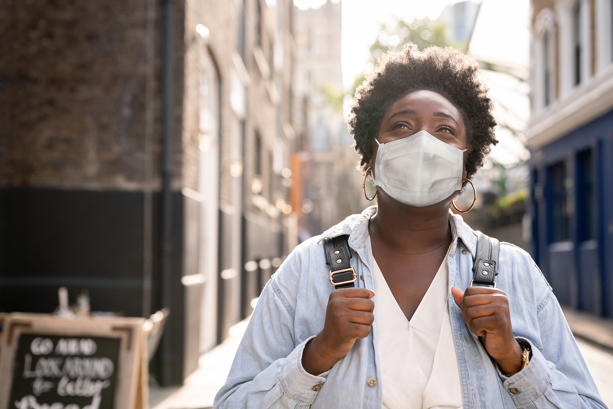 Thoughtful black woman wearing a facemask on the street